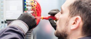 Closeupen av elektrikerteknikern arbetar med trådar för elektrisk kabel fotografering för bildbyråer