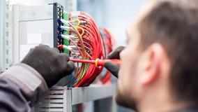 Closeupen av elektrikerteknikern arbetar med trådar för elektrisk kabel arkivbild