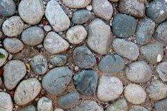 Closeupen av en gammal pebblestoneväg lappade med naturliga stenar Arkivfoton