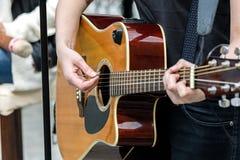 Closeupen av en kvinna räcker att spela den akustiska gitarren utomhus royaltyfria bilder