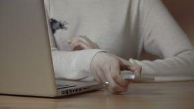 Closeupen av en kvinnlig räcker upptagen maskinskrivning på en bärbar dator lager videofilmer