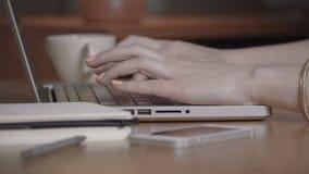 Closeupen av en kvinnlig räcker upptagen maskinskrivning på en bärbar dator arkivfilmer