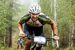 Closeupen av en manlig cyklist rider till och med skog, honom har en smutsig framsida Royaltyfri Foto