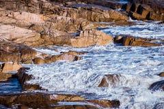 Closeupen av en våg som bryter försiktigt över grunt, vaggar på kusten royaltyfria foton