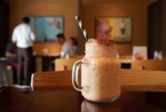 Closeupen av ett smakligt thailändskt mjölkar te på en tabell i ett kafé med en suddig bakgrund royaltyfria foton
