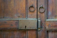 Closeupen av ett träåldrigt låser och två rostade cirkeldörrknackare över en utsmyckad trädörr royaltyfria foton