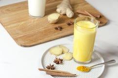 Closeupen av exponeringsglas av guld- mjölkar med spieces Varm latte för gurkmeja med örter Sund strikt vegetariandryck royaltyfria bilder