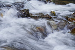 Closeupen av flödande vatten över vaggar arkivfoton