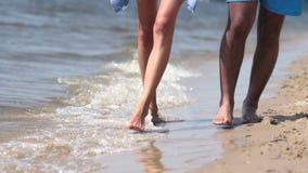 Closeupen av fot som går i vatten, kantar på stranden lager videofilmer