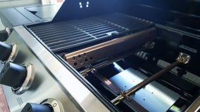 Closeupen av gasbrännare för gasgrillfestgallret, flavorizerstänger, porcelanized gjutjärnraster och kontrollknoppar arkivfoto