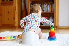Closeupen av gulliga små 12 månader gammalt litet barn behandla som ett barn flickabarnsammanträde på potta Arkivfoton