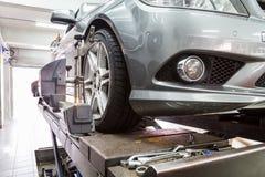 Closeupen av gummihjulet som klämmas fast med tillrättaren som genomgår det auto hjulet, arrangera i rak linje royaltyfri fotografi