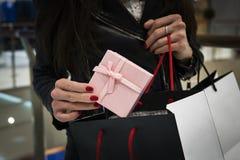 closeupen av handen av en ung caucasian kvinna med hennes fingernaglar målade rött rymma en svart shoppa påse av gåvor buying arkivbilder