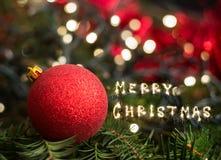 Closeupen av julgrangarneringar med glad jul undertecknar Arkivbild