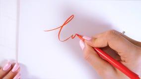 Closeupen av kalligrafhänder skriver ordet FÖRÄLSKELSE på vitbok Inskriva dekorativa dekorerade bokstäver calligraphy arkivfilmer
