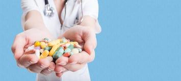 Closeupen av kvinnadoktorn räcker hållande preventivpillerar arkivfoton