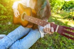 Closeupen av kvinnan r?cker att spela den akustiska gitarren parkerar eller arbeta i tr?dg?rden p? bakgrund Ton?rig flicka som l? royaltyfria foton