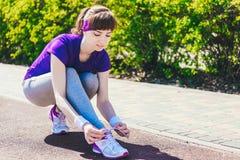 Closeupen av kvinnan som binder skon, snör åt Kvinnlig sportkonditionlöpare som får klar för att jogga utomhus på skogbanan arkivbilder