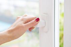 Closeupen av kvinnans hand öppnar ett fönster Royaltyfri Bild