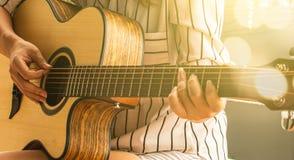 Closeupen av kvinnans hand rymmer en klassisk gitarr royaltyfri fotografi