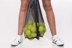 Closeupen av kvinnlign lägger benen på ryggen hållande tennisbollar i ingrepp i studioEn Royaltyfri Bild