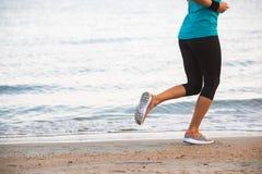 Closeupen av kvinnlign lägger benen på ryggen spring på stranden på soluppgång i morgon Royaltyfria Foton
