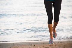 Closeupen av kvinnlign lägger benen på ryggen spring på stranden på soluppgång i morgon Royaltyfri Fotografi