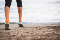 Closeupen av kvinnlign lägger benen på ryggen spring på stranden på soluppgång i morgon Royaltyfri Bild