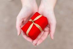 Closeupen av kvinnlign räcker att rymma en liten röd gåva med en golde Fotografering för Bildbyråer