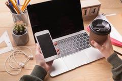 Closeupen av kvinnlign räcker den hållande smartphone- och kaffekoppen Arkivfoton