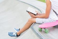 Closeupen av läsning för den unga mannen på skateboarden parkerar fotografering för bildbyråer