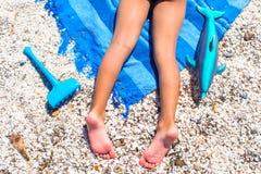 Closeupen av lilla flickan lägger benen på ryggen på den tropiska stranden med Royaltyfri Bild