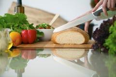Closeupen av människan räcker matlagning i kök på den glass tabellen med reflexion Hemmafru som skivar bröd Royaltyfri Foto