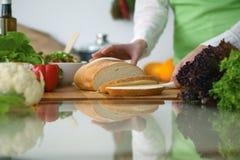 Closeupen av människan räcker matlagning i kök på den glass tabellen med reflexion Hemmafru som skivar bröd Royaltyfri Fotografi