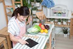 Closeupen av m?nniskan r?cker matlagning i k?k genom att anv?nda handlagblocket Sunt m?l, vegetarisk mat och livsstilbegrepp arkivfoto
