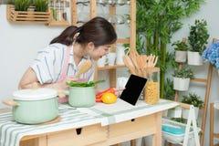 Closeupen av m?nniskan r?cker matlagning i k?k genom att anv?nda handlagblocket Sunt m?l, vegetarisk mat och livsstilbegrepp royaltyfri foto