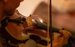 Closeupen av musikerns hand spelar en fiol i en orkester arkivfoton