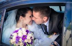 Nygift person kopplar ihop att kyssa i bröllopbil Royaltyfri Bild