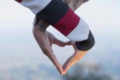 Closeupen av par som gör hjärtaform med händer, kopplar ihop förälskat, fokusen på händer, man- och kvinnaturister i bergen på so arkivfoto