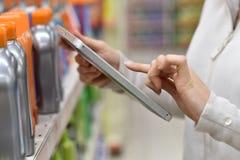 Closeupen av person som ägnar sig åt handel som använder minnestavlan shoppar in arkivfoto