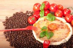 Closeupen av pizza med kaffebönor, röda två dela sig, tomater, ost och basilika på träbakgrund Arkivbilder
