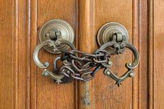 Closeupen av två antikvitetkopparutsmyckade dörrknackare över en åldrig träutsmyckad dörr stängde sig med den rostade kedjan och  royaltyfri fotografi