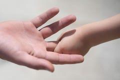 Closeupen av två tryckande på händer av litet behandla som ett barn på pojkeinnehavfingret av den manliga fadern som symbol av fa arkivbilder