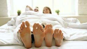 Closeupen av unga härliga och älska par spelar och dansar deras fot under filten medan vaken upp i säng i morgon stock video