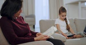 Closeupen en gammal farmor läste en bok och att se hur hennes brorsdotter som spelar i en smartphone en lek, medan sitta på sof stock video