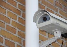 Closeupen för bevakningkameran monterade på den gula tegelstenväggen Royaltyfri Bild