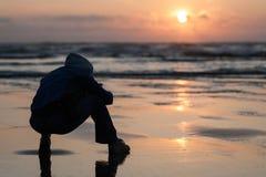 Closeupen för uddeutkiksolnedgången med mankonturn sitter på stranden Royaltyfri Foto