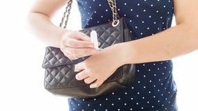 Closeupen isolerade fotoet av den unga kvinnan som tar den menstruations- tampongen ut ur handväskan Royaltyfria Bilder