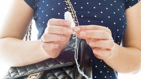 Closeupen isolerade fotoet av den unga unga kvinnan som tar tampongen ut ur hennes påse Royaltyfria Bilder