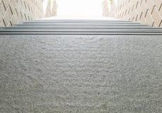 Closeupen kliver ner modellen av stentrappan med suddig texturerad bakgrund för stentegelstenväggen under solljus i eftermiddagen Fotografering för Bildbyråer
